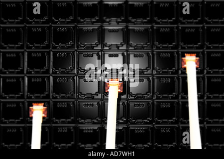 Concept image of three telephone jacks plugged into wall of plugs - Stock Photo
