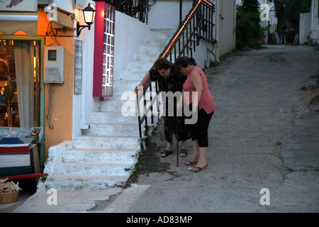 Old women with a walking stick getting some help from another woman Platanias, Crete, Greece - Stock Photo