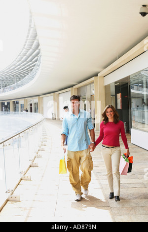 Mid adult man and a mature woman walking in a shopping mall - Stock Photo