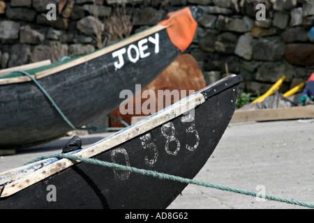 Two currachs pointed nosed seagoing craft one named Joey soft focus tied to a stone sea wall awaiting the tide - Stock Photo