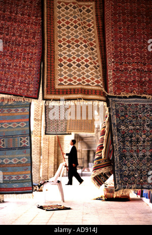 Carpets hanging elaborate geometric brickwork walls of the 14th century Ouled El Hadef quarter in the caravan town - Stock Photo