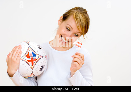 woman with a football and austrian flag, laughing - Stock Photo