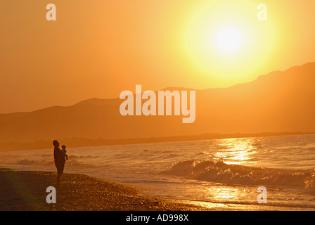 CRETE, GREECE. A father and baby child watching the sun set over the Rodhopou Peninsula from the beach at Maleme - Stock Photo