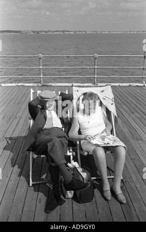 Older couple on holiday sitting in deck chairs on the pier. Southend on Sea  Essex  England 1974 1970s UK HOMER - Stock Photo