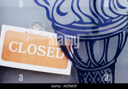Detail of iconic image of an ice cream cone on a shop or kiosk window with a faded sign saying Closed - Stock Photo