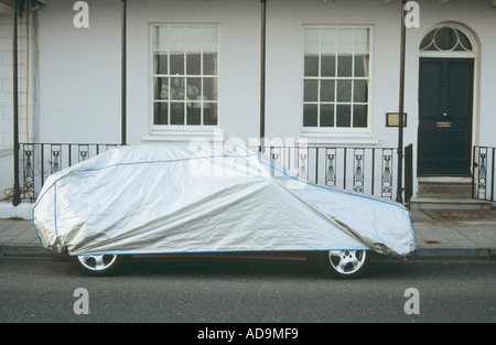 Car protected by a grey plastic sheet sitting on roadside outside a smart white Georgian terraced house with black - Stock Photo