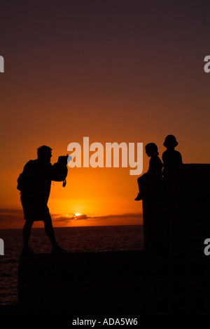 father taking picture of two sons in the sunset - Stock Photo