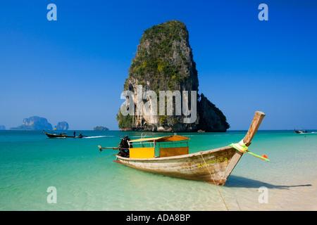 Anchored boat chalk cliff in background Phra Nang Beach Laem Phra Nang Railay Krabi Thailand - Stock Photo