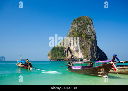 Anchored boats chalk cliff in background Phra Nang Beach Laem Phra Nang Railay Krabi Thailand one year after the - Stock Photo
