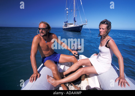 Couple on dinghy yacht in background Pigeon Point Tobago Trinidad And Tobago - Stock Photo