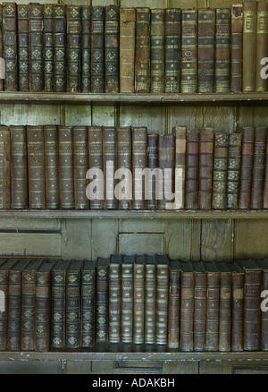 Very old historical traditional bookcase covered in old large books placed in a large Norfolk properties library - Stock Photo