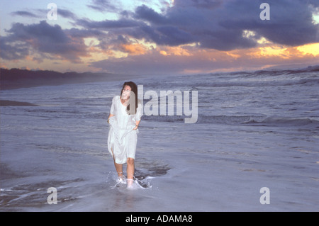 Woman Splashing and Having Fun at Barking Sands Beach Park Kauai Hawaii - Stock Photo