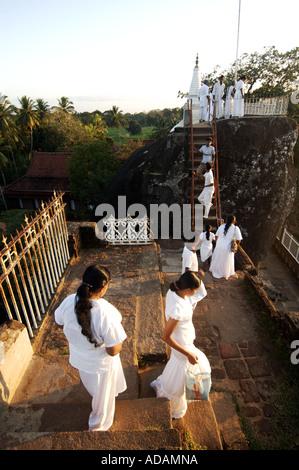 Anuradhapura buddhist pilgrims visit the Isurumuniya Vihara pagoda site at sunset