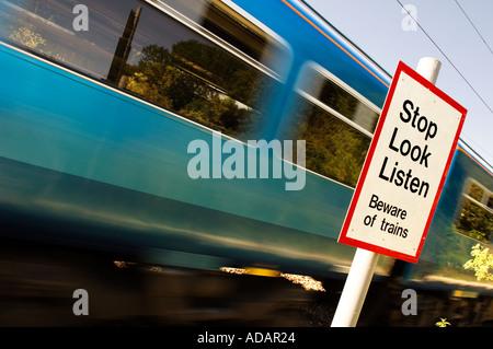 Train speeding through a pedestrian rail crossing with warning sign - Stock Photo