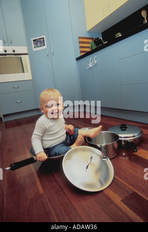 1 year old baby boy sitting in pots in kitchen - Stock Photo