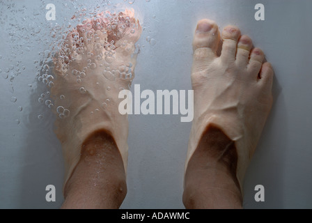 Man's feet submerged in a bathtub - point of view. - Stock Photo
