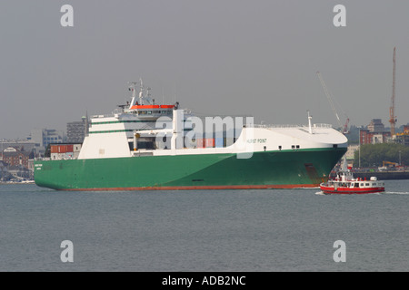 Large commercial container ship leaving Southampton docks entering Southampton Water seen from Hythe Hampshire with - Stock Photo