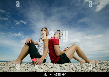 Couple on beach sitting back to back listening to personal mp3 players - Stock Photo