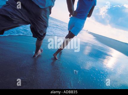 Couple running barefoot on a beach - Stock Photo