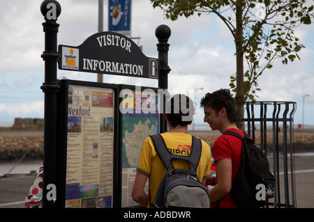 two young male spanish tourists with backpacks look at visitor information sign in wexford town - Stock Photo