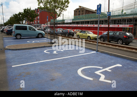 disabled parking bays in car park with one car parked in disabled bay next to railway line and construction site - Stock Photo