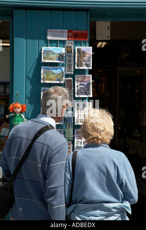 elderly couple looking at postcard display outside a tourist souvenir shop in avoca county wicklow - Stock Photo