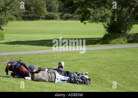 tourists lying on the grass soaking up the sun with backpacks open ground in grounds of glenalough monastic site - Stock Photo