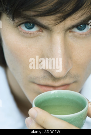 Man holding up cup of tea to mouth, looking at camera - Stock Photo