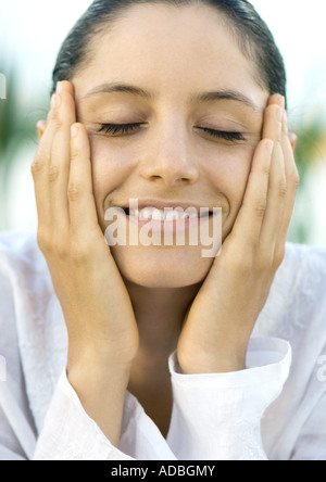 Woman holding face in hands, smiling, eyes closed, close-up - Stock Photo