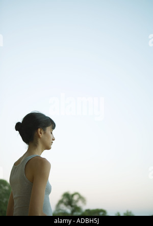 Woman outside with eyes closed at twilight - Stock Photo