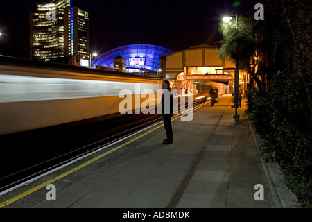 Photo showing someone waiting for a tube train with earls Court and Empress State buildings in the background - Stock Photo