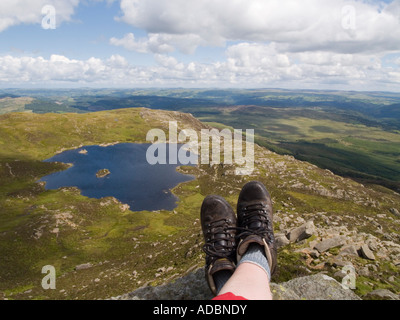 Pair of feet wearing walking boots in foreground with view down to Llyn y Foel from Moel Siabod Daear Ddu east ridge - Stock Photo