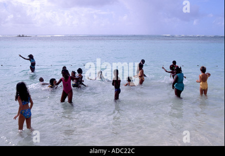 Sainte Anne part of the waterfront with youngsters splashing around in the sea at seaside resort - Stock Photo