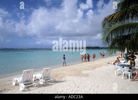 Sainte Anne part of the sandy beach with palm tree and holidaymakers at  seaside resort tropics tropical - Stock Photo