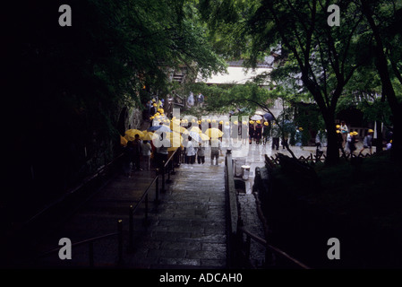 A group of Japanese school children holding yellow umbrellas at Kiyomizu dera temple in Kyoto Japan - Stock Photo