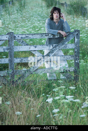 Teen boy listening to earphones, leaning against wooden fence - Stock Photo