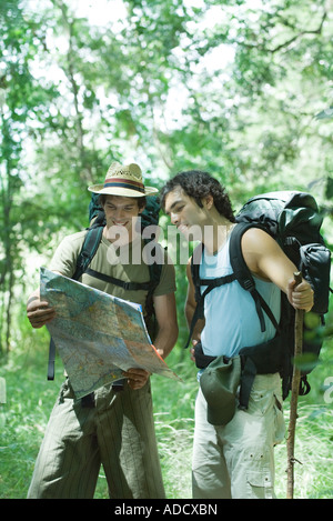 Two hikers standing in forest, studying map - Stock Photo