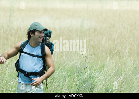 Young male hiker walking through field, looking away, smiling - Stock Photo