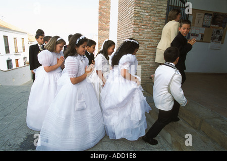 Children in white dresses and sea officers uniforms entering church for their first communion Periana Malaga Spain - Stock Photo