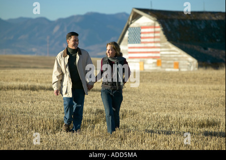 Man and women walking through cut grass fields in Fall with barn and american flag Colorado - Stock Photo