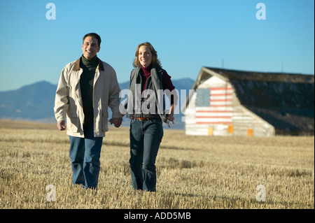 Man and women smiling walking through cut grass fields in Fall with barn and american flag Colorado - Stock Photo