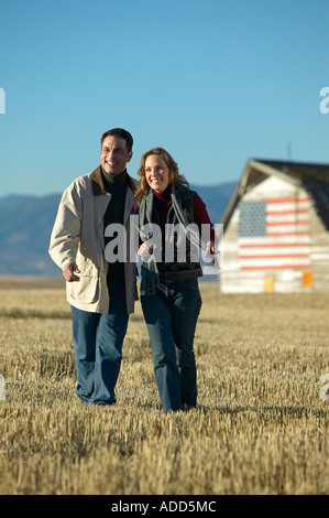 Man and women smiling walking through cut grass fields in Fall with barn american flag behind them Colorado - Stock Photo