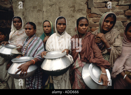 Poor people with pots queuing for food for their families at Mother Teresa s Mission Calcutta India - Stock Photo