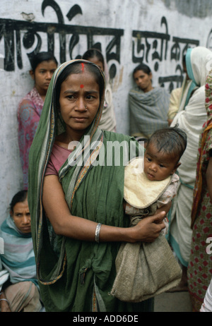 Mother carrying child queuing for food with other women at Mother Teresa Mission Calcutta India