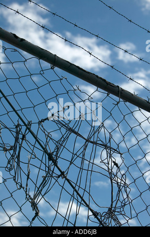 Mended chain link fence with barbed wire against blue sky and clouds - Stock Photo