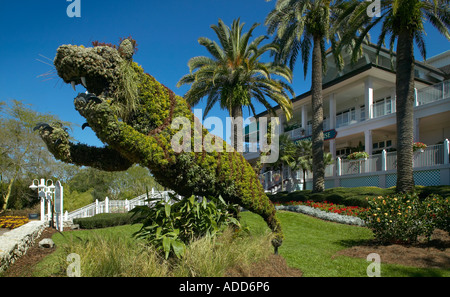 Topiary shaped like a pouncing lion and tropical palm trees in front of a white house with pillars - Stock Photo