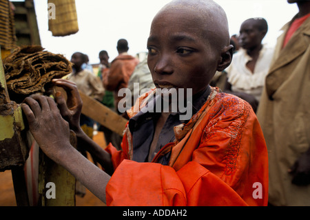 A weak young child arriving at a way station on the way back to Kigali the Rwandan capital. - Stock Photo