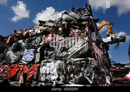 Cubes of crushed cars stand in a huge pile as a crane lifts a Fiat Bravo into the crusher - Stock Photo