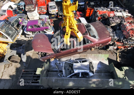 Cubes of crushed cars stand in a huge pile at a car recycling and salvage yard - Stock Photo
