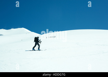Skier going across snowy landscape, looking toward group of skiers in distance - Stock Photo